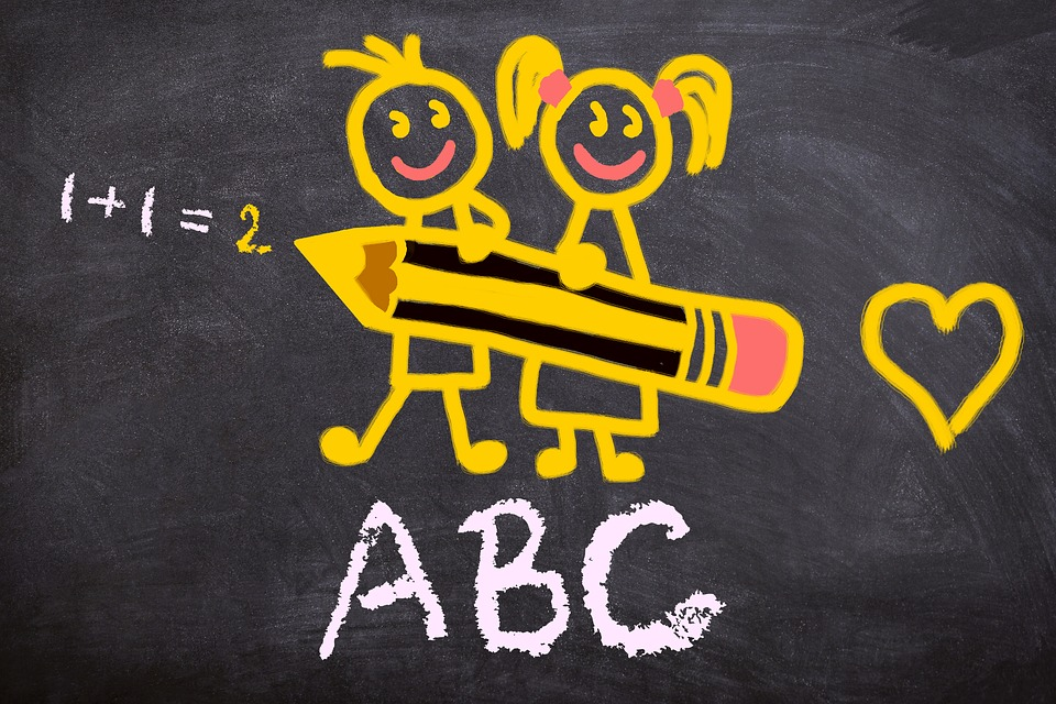 chalkboard with sketch illustration of two children holding a pencil, one plus one equals two, ABC, and a heart